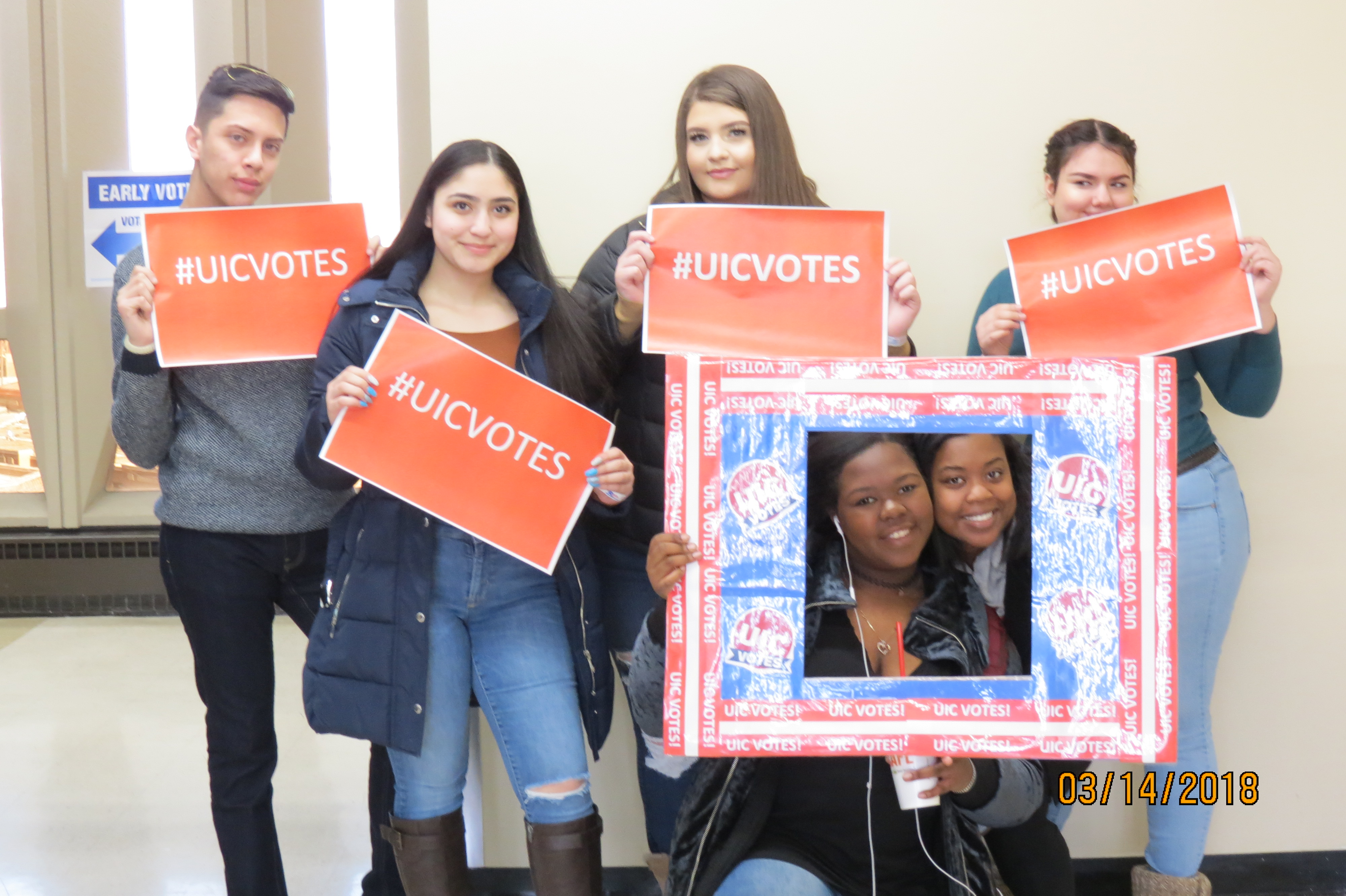 6 students stand together displaying signs that say #UICVOTES