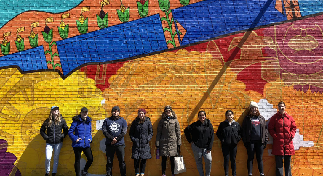 UIC volunteers at El Paseo Community Garden stand in front of a mural