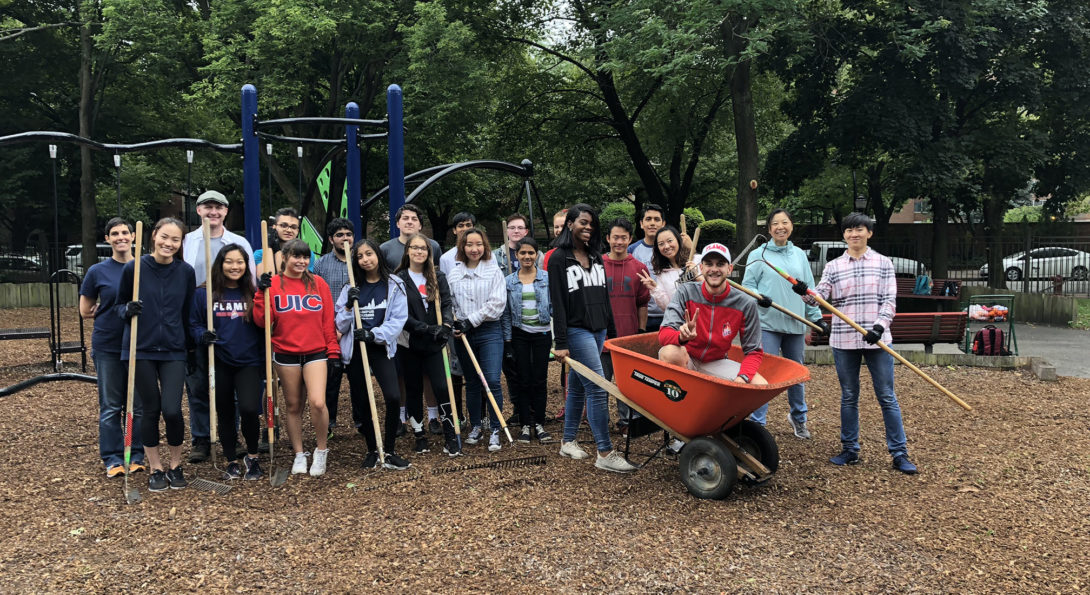 Volunteers with rakes and wheelbarrow at park
