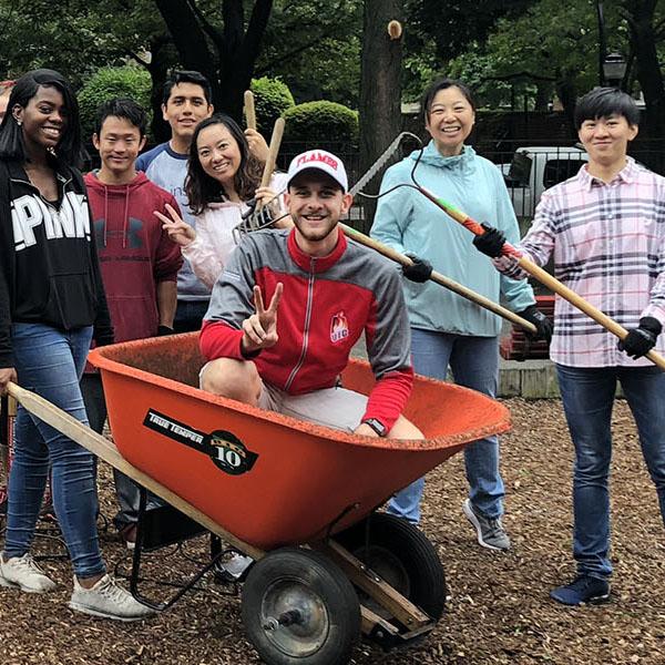 Volunteers with wheelbarrow and rakes in park