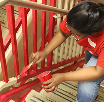 Student painting stair railing during MLK day