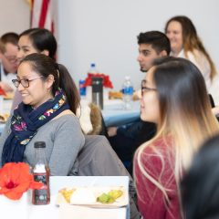 Students smiling at guest speaker during lunch