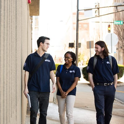 Three people in AmeriCorps VISTA Volunteer navy blue polos walking and smiling at each other