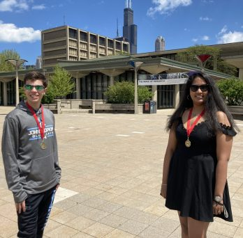 Student Travis Connor Brones on left with leadership certificate medallion around next and student Shraddha Shetty on right with leadership certificate medallion around neck, standing in the quad.
