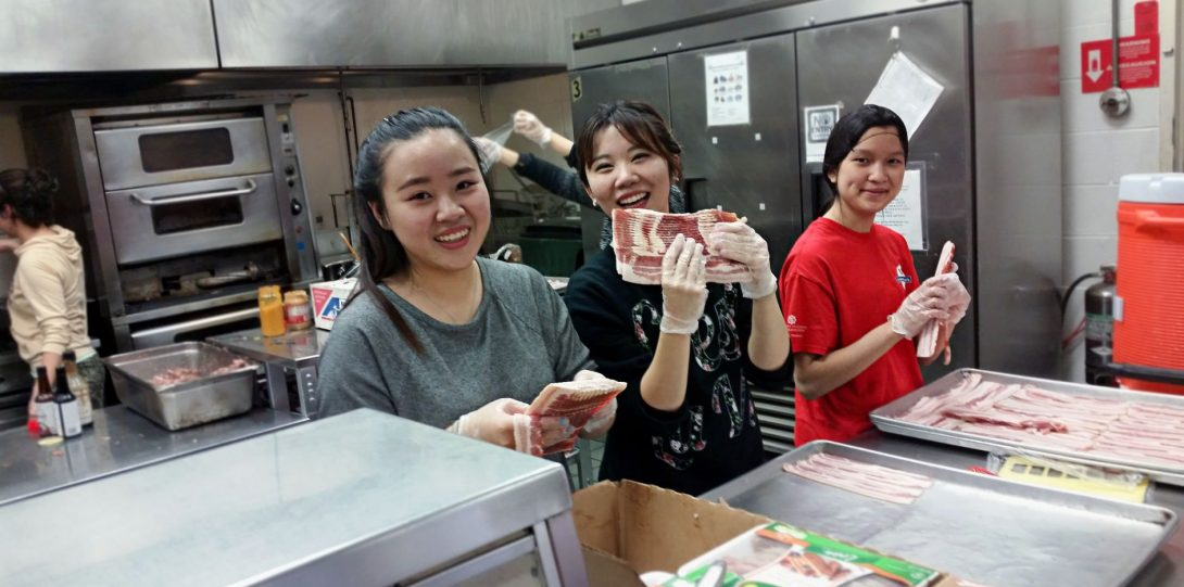 Smiling students in an industrial kitchen holding up raw bacon that they are separating onto large trays to be cooked