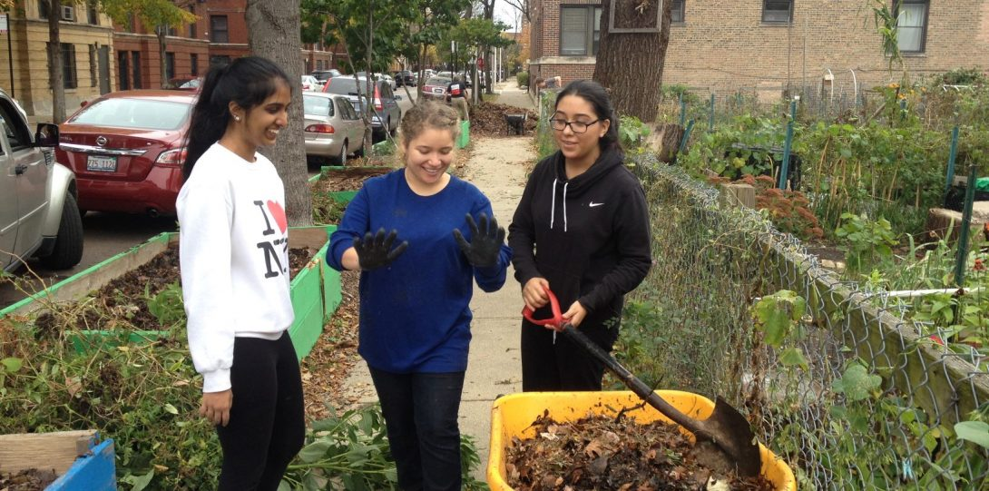 Three students smiling and laughing while standing on sidewalk near community garden, with a yellow wheelbarrel of dirt in front