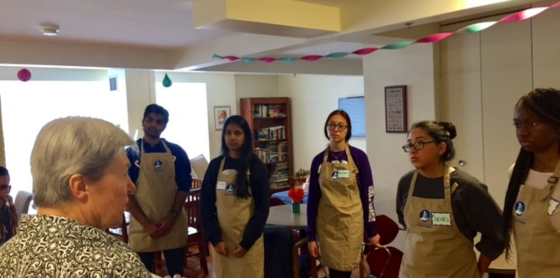 Group of students in aprons standing in room with streamer decorations looking at and listening to older person speaking