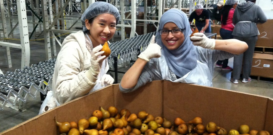 Two students holding pears and smiling with thumbs up in front of a large box of pears in a wearhouse setting